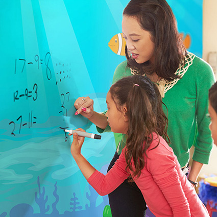 Image showing a writable wall in school where a student girl writing on it