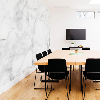 Surface wall design in a room with black chairs image